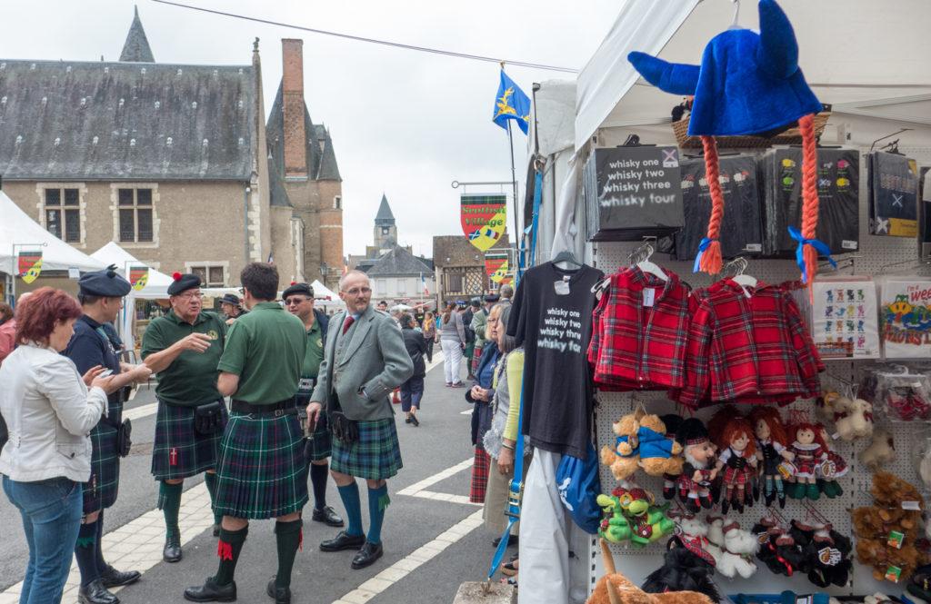 Des hommes en kilt sont à côté d'un stand du marché