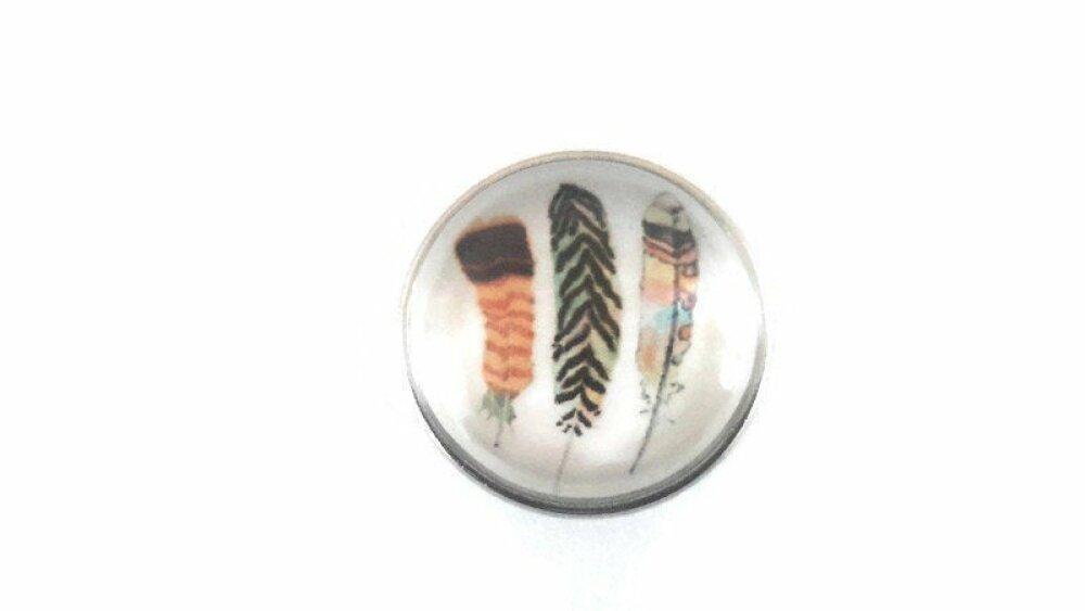 bouton pression à cabochon de verre 18mm à 3 plumes noires, jaunes et orangées sur fond blanc.