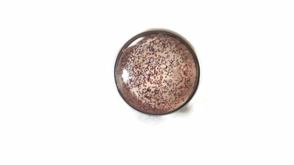 bouton pression à cabochon de verre à paillettes marron  sur fond beige