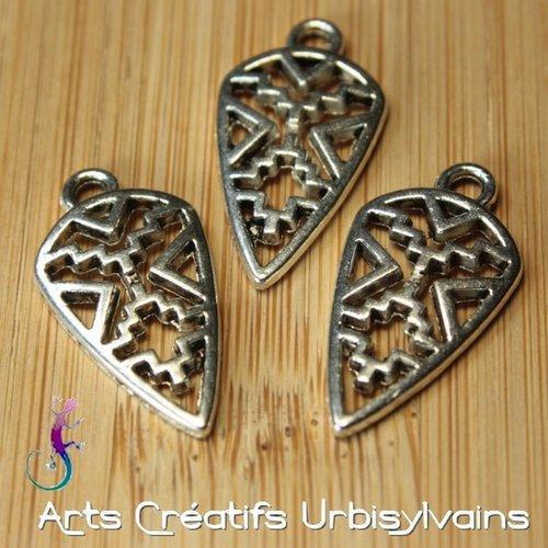 Un pendentif ou charm breloque motif ethnique en métal argenté