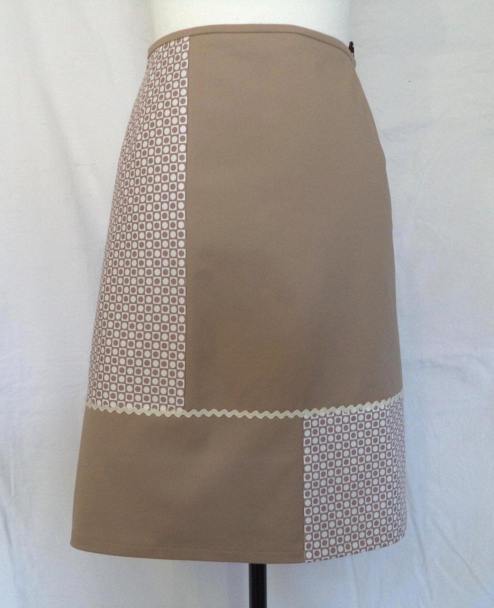 Jupe trapèze beige, coton extensible, avec découpes asymétriques sur le devant.