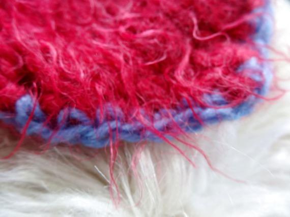 mitaine en laine rouge , ajout d'une bande bleue et d'une broche sur l'une d'elles: pénélope