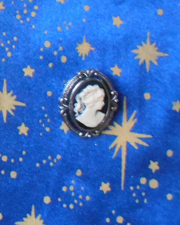 Broche en alliage argent/étain avec camée en résine marquise beige sur fonds noir.