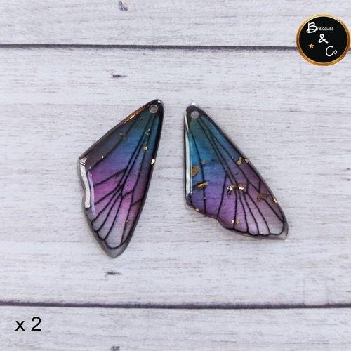 Pendentif en résine aile de papillon / de fée  -  couleur violet / bleu avec pailletes or -  percées - 2 unités