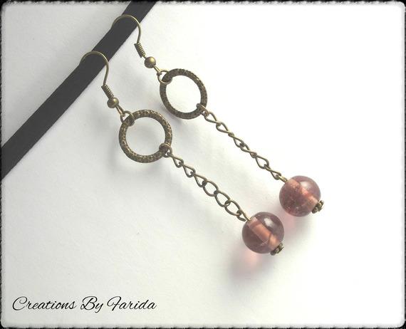 Boucles d'oreilles bronze pendante avec une perle violette sous un anneau