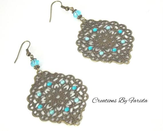 Boucles d'oreilles bronze pendante avec une estampe et des strass bleues