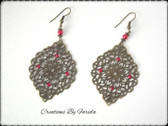 Boucles d'oreilles bronze pendante avec une estampe et des strass rouge et argenté