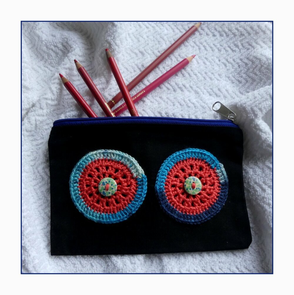 Trousse en coton noir avec des yeux multicolore au crochet fait-main