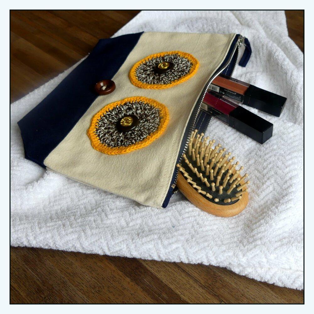 Trousse de toilette écrue et bleue marine en coton brossé avec yeux marron et jaunes au crochet fait-main