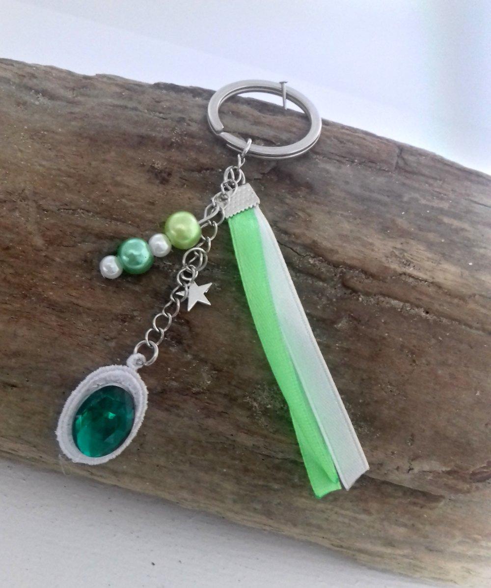 Bijoux de sac  ou porte clés avec sa broderie en dentelle blanche avec son strass vert et de ses breloques