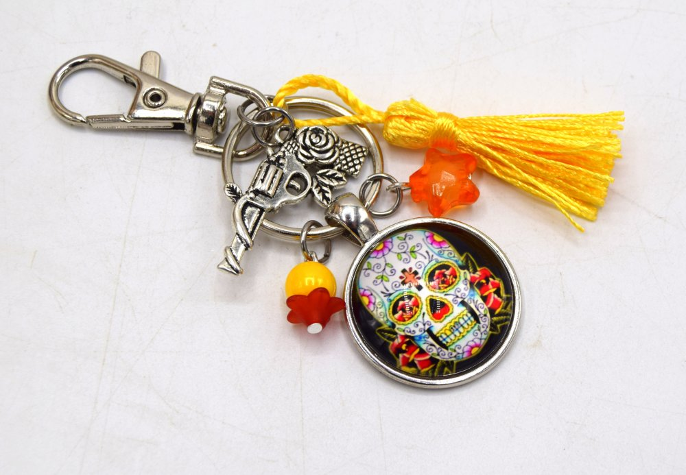 Porte clé Crâne fleuris avec son pistolet entouré d'une rose & étoile jaune, décoration sac à main, bijoux cabochon pompon.
