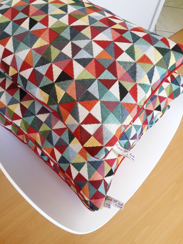 Housse de coussin aux motifs géométriques multicolores à dominance de rouge