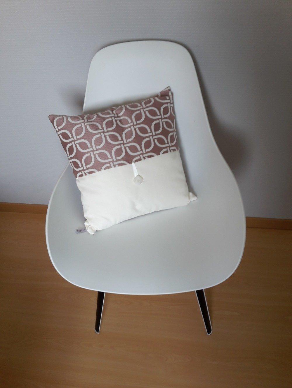 Housse de coussin aux motifs géométriques en rose poudré et blanc cassé au style graphique moderne