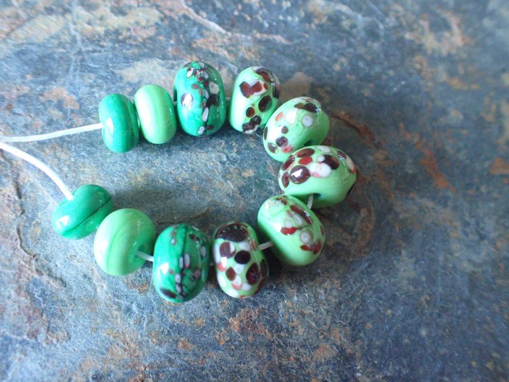 Un ensemble de 11 perles en verre de Murano, filées au chalumeau dans les tons verts