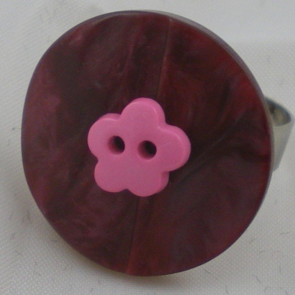Bague composée d'un bouton mauve et d'un bouton rose fixés sur un support de bague ajustable