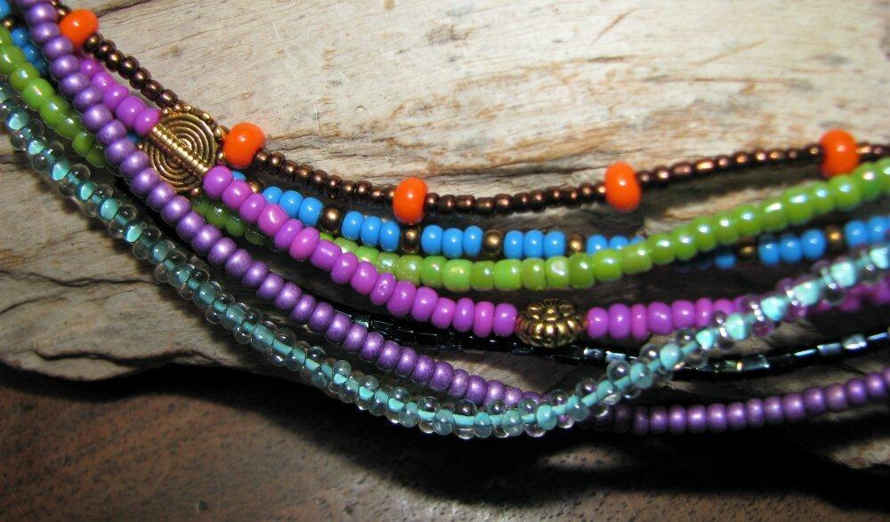 """Collier """"Tzigane"""" en lin et 7 rangées de rocailles et perles de métal dans les tons de violet, bleu, vert... et bronze."""