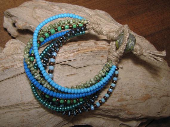 Bracelet  en lin et  7 rangées de rocailles et perles de verre dans les tons de bleu et vert
