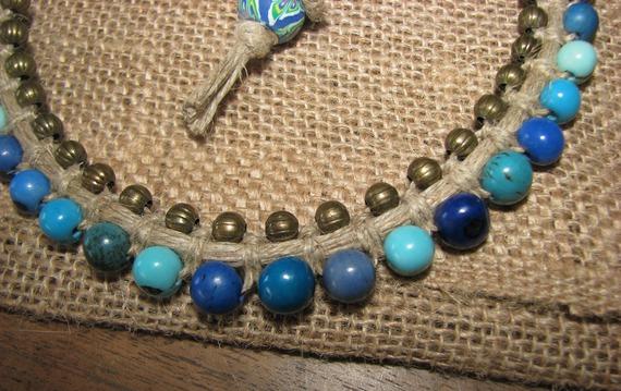 Collier court en graines d'açaï dans les tons de bleu et petites perles bronze tissées dans