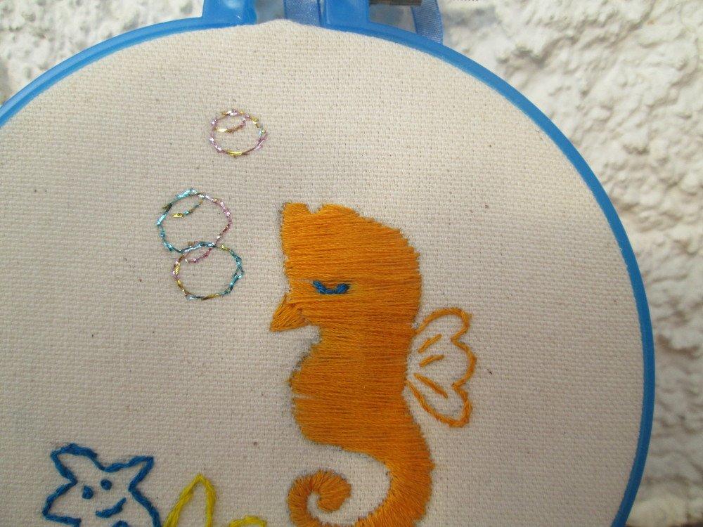 Décoration petit hippocampe orange avec étoiles de mer.