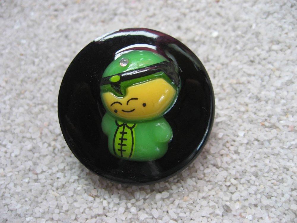 Grande bague kawaii, poupée verte, sur fond noir en résine / Diamètre 35mm