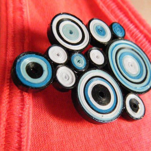 1 broche / badge en quilling de couleur bleu, blanc et noir