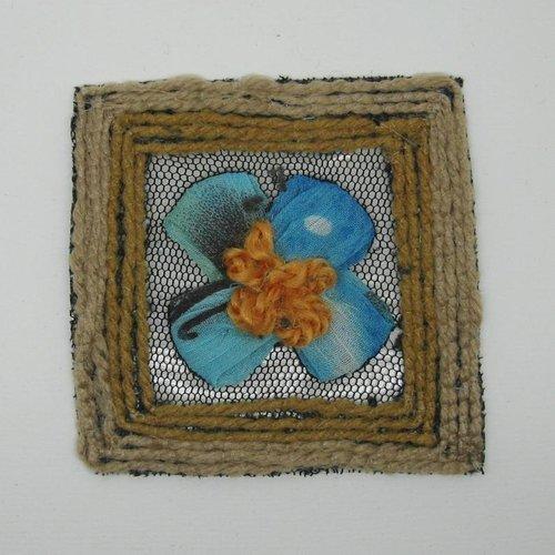 Application écusson carré bordure en laine beige, centre fleur tissu voile dégradé vert et bleu avec cœur en laine orange