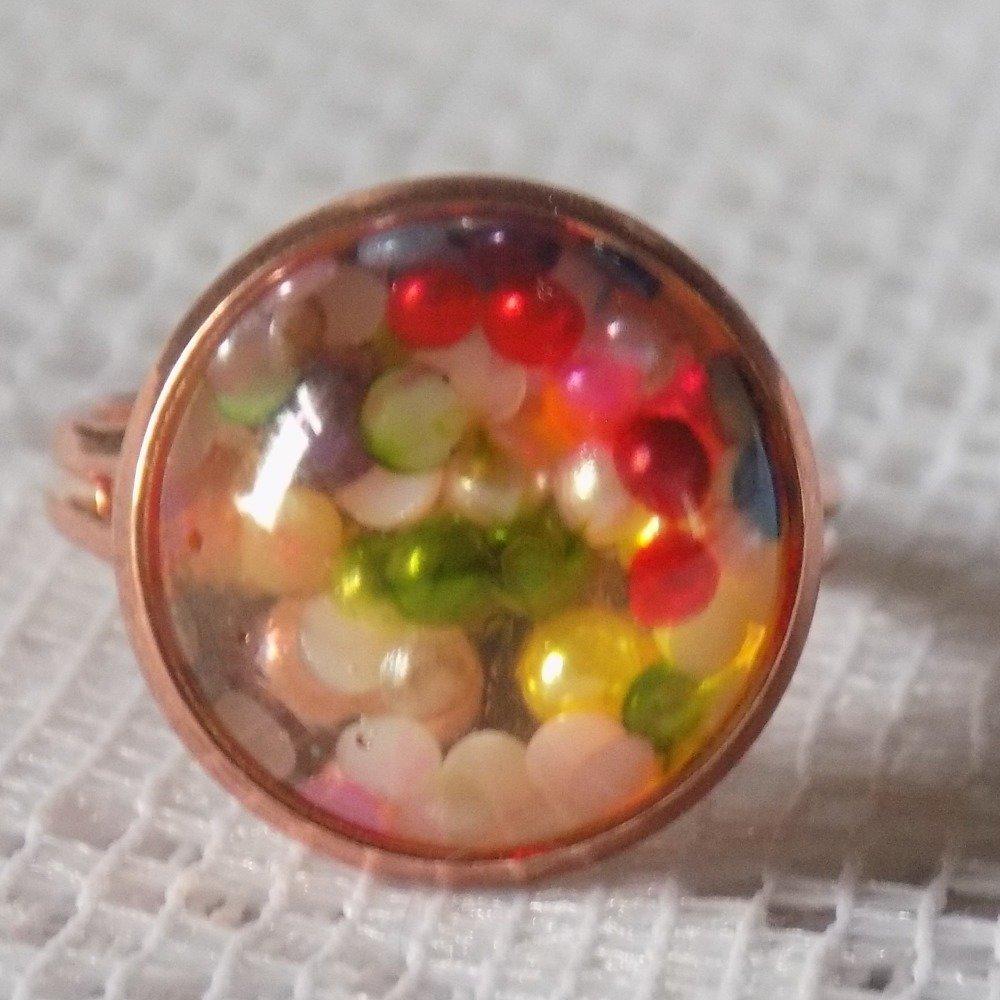 Bague ajustable dorée rose,ronde,cabochon résine avec incrustation petites perles multicolores.