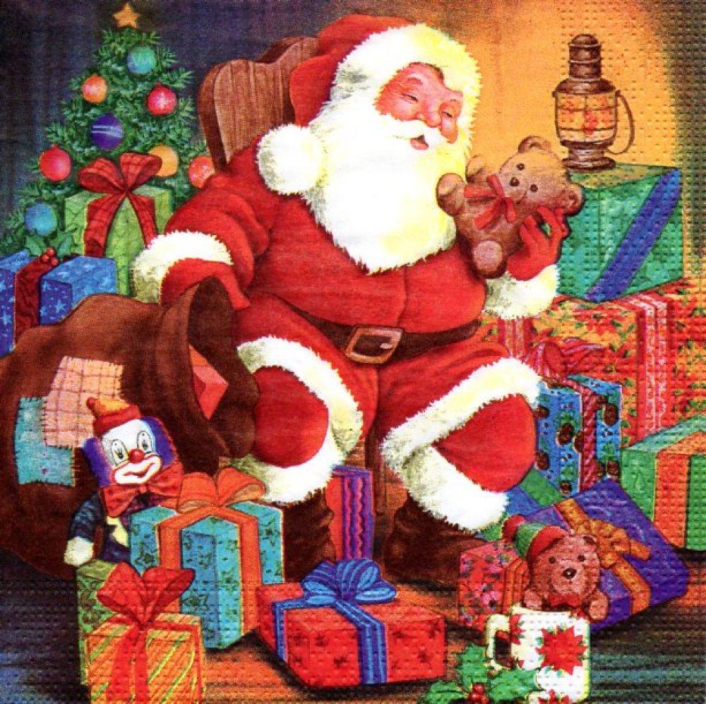 Serviette en papier Père Noël assis au milieu des cadeaux avec un ourson
