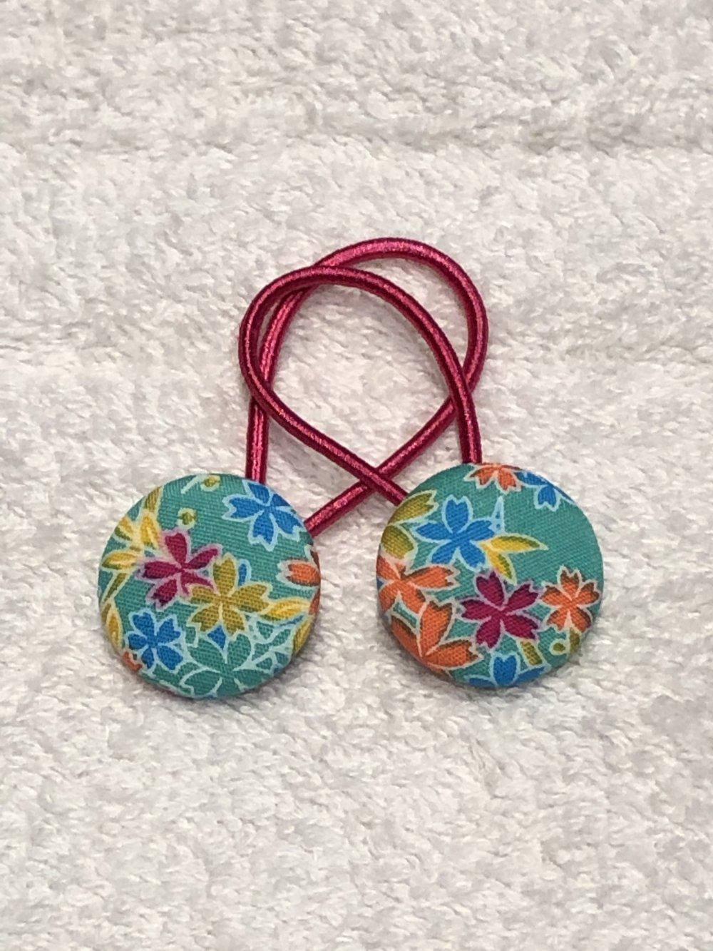 2 Elastiques cheveux fleurs multicolores fond turquoise
