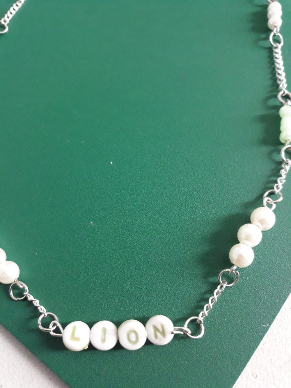 Un collier en argent en mailles fines, avec des perles en cristal blanc et des vertes  des perles incrusté de lettres