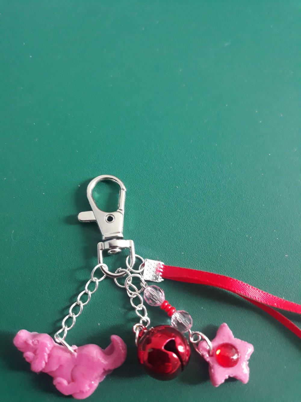 Un bijoux de sacs ou porte clef avec 3 breloques un grelot et 2 en porcelaine froide et un ruban de satin rouge