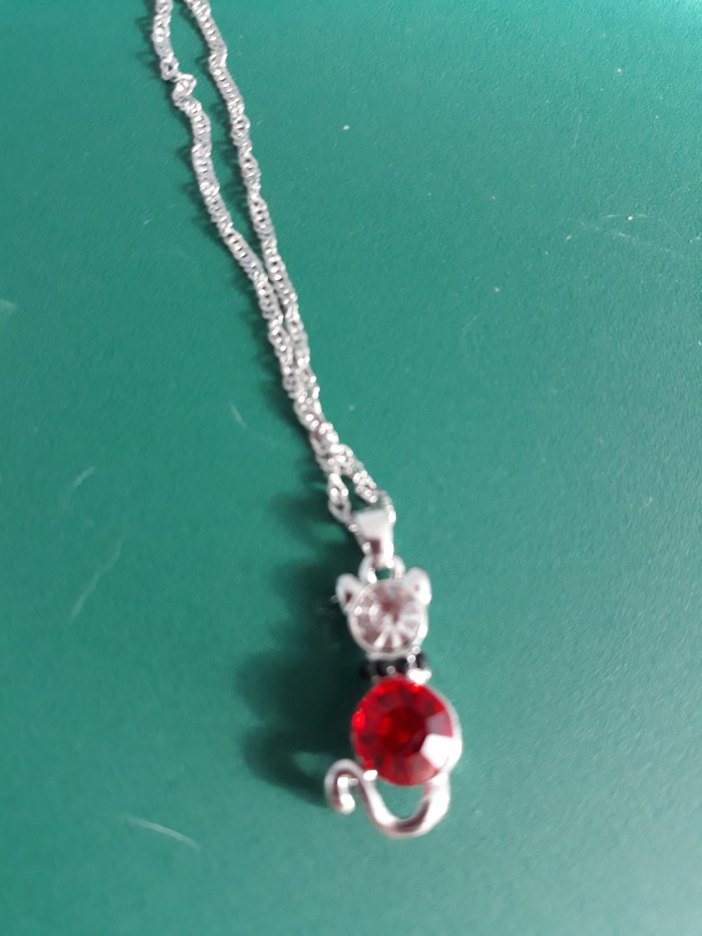 Un collier ras cou réglable en métal argenté avec pendentif chat incrusté de perles de cristal