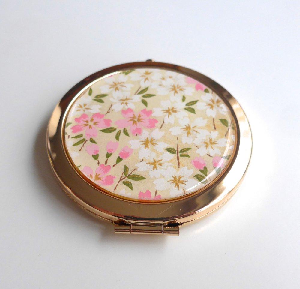 Miroir de poche rond, doré, recouvert de papier washi au motif de fleurs blanches et roses, et d'un cabochon en résine.