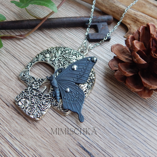 Collier crâne argenté et papillon noir