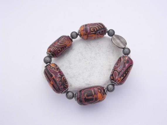 bracelet avec perles allongées oranges et bordeaux en pâte polymère