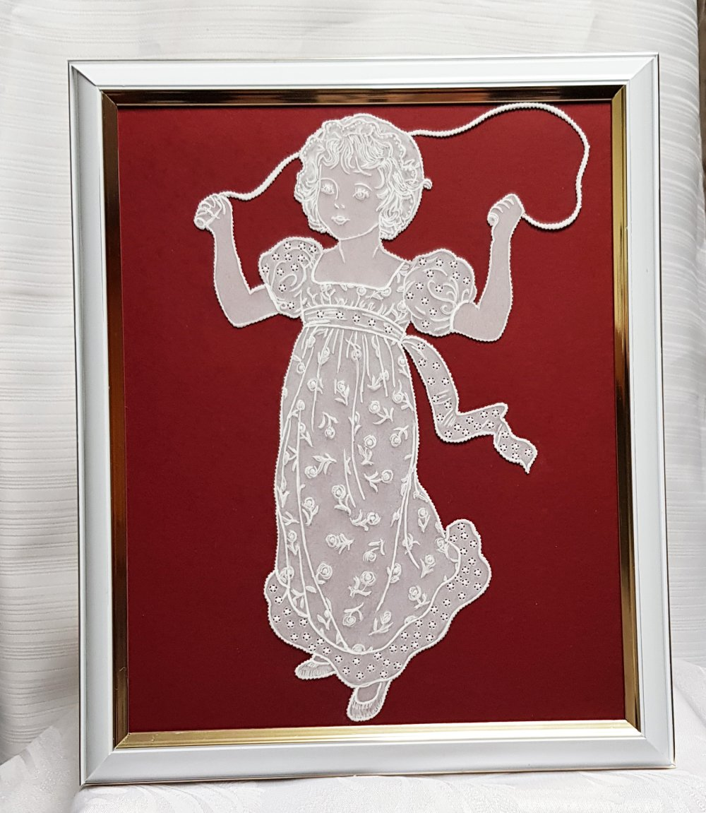 Tableau cadre blanc orné d'une fillette en papier parchemin sautant à la corde .