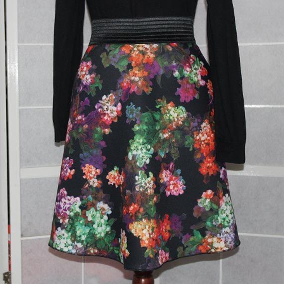 Jupe taille élastique forme trapèze ample en jersey fleurs multicolores sur fond noir