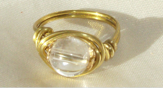 Bague sur mesure avec du fil d'aluminium doré et une perle de Cristal de roche