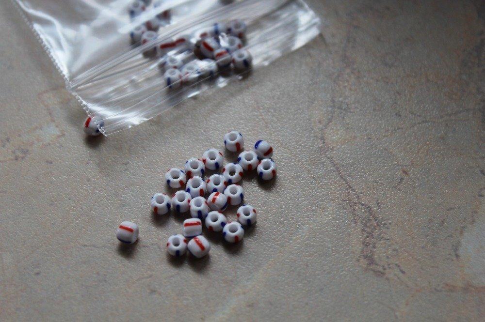 Perles grosse rocaille blanches rayées de rouge et de bleu