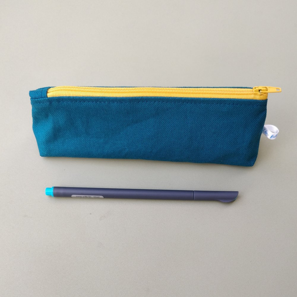 Trousse à crayons doublée, coton bleu pétrole et doublure à motifs géométriques jaunes.